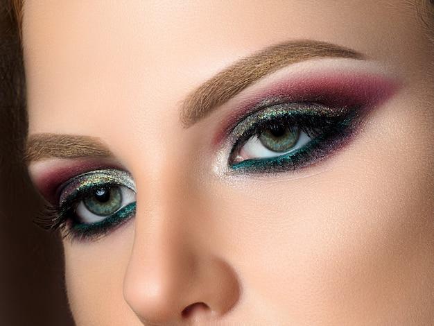 Bliska niebieskie oczy kobiety z pięknym wielobarwnym makijażem smokey eyes. makijaż nowoczesnej mody. strzał studio