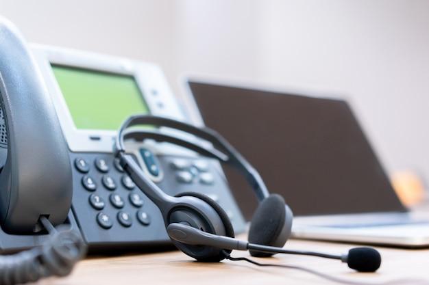 Bliska nieostrość na zestawach słuchawkowych z urządzeniami telefonicznymi na biurku w celu obsługi klienta