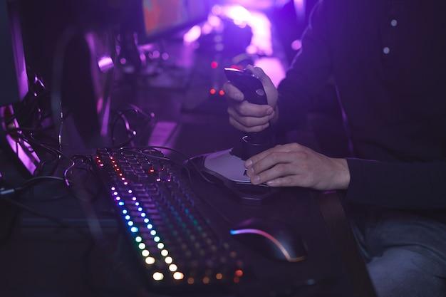 Bliska nierozpoznawalnego człowieka za pomocą joysticka wyścigowego podczas grania w gry wideo w ciemnym pokoju, kopia przestrzeń