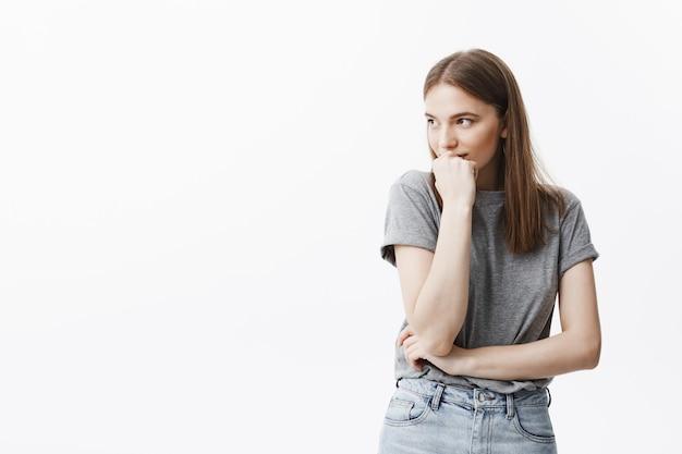 Bliska nieśmiała śliczna ciemnowłosa europejska studentka w swobodnej szarej koszulce, patrząc na bok z zrelaksowanym i spokojnym wyrazem twarzy, trzymając głowę ręką, myśląc o ukochanej osobie.