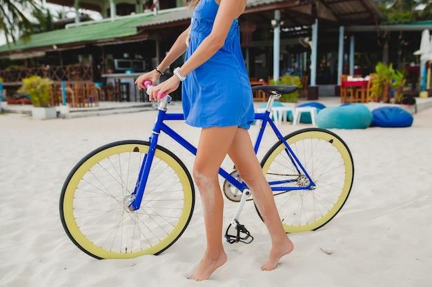 Bliska nogi atrakcyjnej kobiety w niebieskiej sukience spaceru na tropikalnej plaży z rowerem