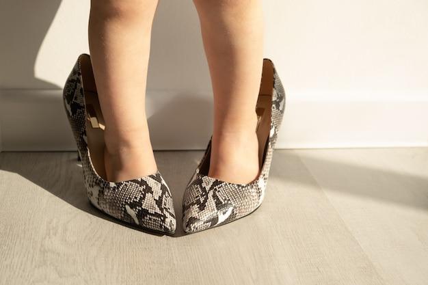 Bliska nogi dziewczynki próbuje jej buty matki w słoneczne popołudnie.