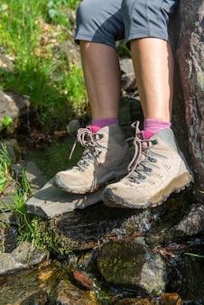 Bliska nogi kobiety w butach turysty