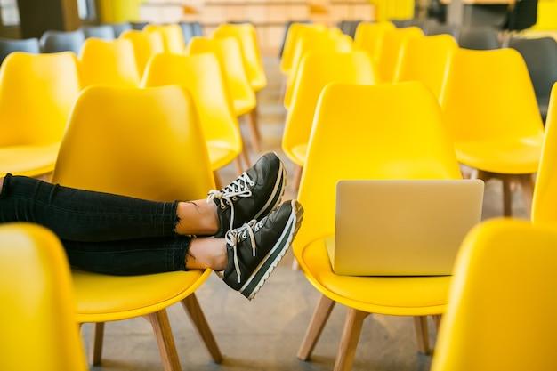 Bliska nogi młodej stylowej kobiety siedzącej w sali wykładowej z laptopem, sala lekcyjna z wieloma żółtymi krzesłami, trampki obuwie, trend w modzie buty