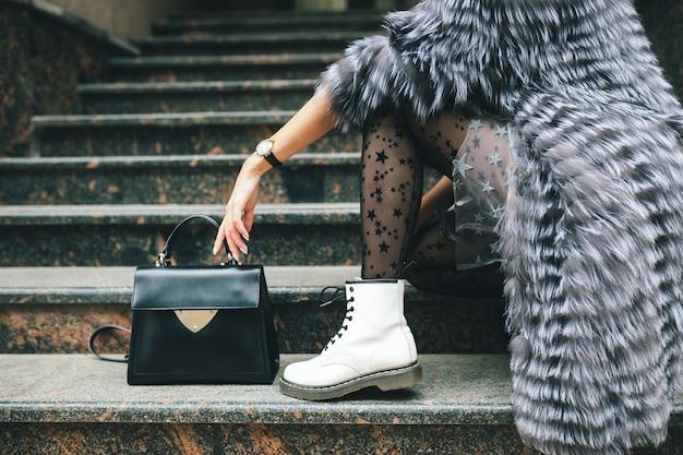 Bliska nogi w białych butach modnej kobiety pozuje w mieście w ciepłym futrze z czarną skórzaną torbą