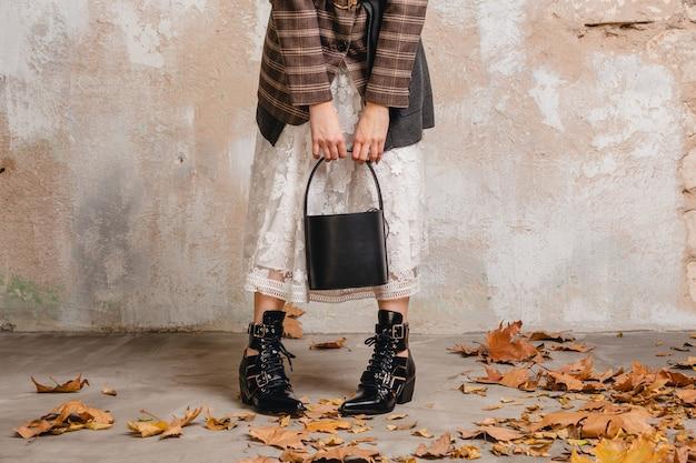Bliska nogi w butach stylowej kobiety w kurtce spaceru przed ścianą na ulicy