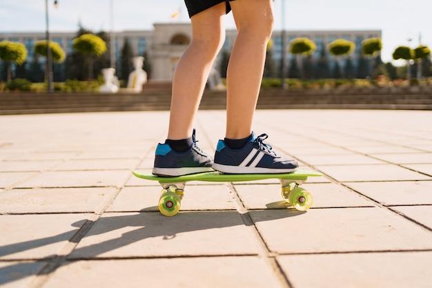Bliska nogi w niebieskie trampki, jazda na zielonej deskorolce w ruchu. aktywny miejski styl życia młodzieży, trening, hobby, aktywność. aktywny sport na świeżym powietrzu dla dzieci. dzieci na deskorolce.