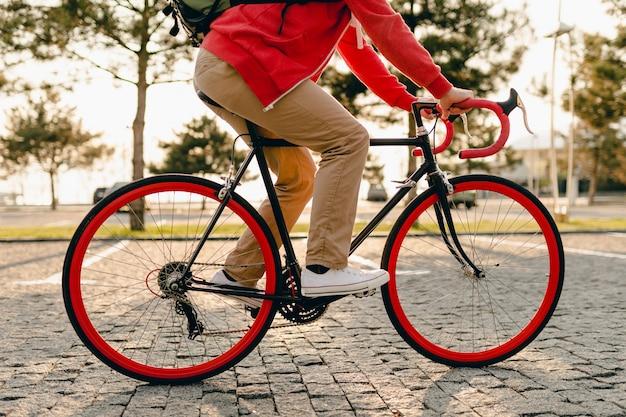 Bliska nogi w trampkach i ręce na kierownicy w stylu hipster brodaty mężczyzna w czerwonej bluzie z kapturem i beżowych spodniach jedzie samotnie z plecakiem na rowerze zdrowy aktywny styl życia podróżnik z plecakiem
