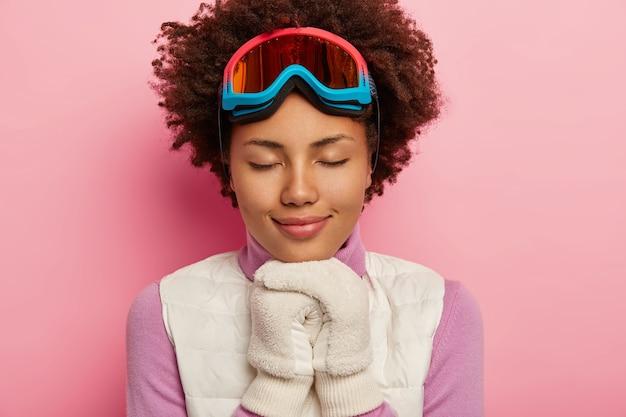Bliska obraz kręconej młodej kobiety ma zrelaksowany, szczęśliwy wyraz twarzy, trzyma ręce w białych rękawiczkach razem, nosi sprzęt snowboardowy, zamyka oczy i delikatnie się uśmiecha, cieszy się zimą