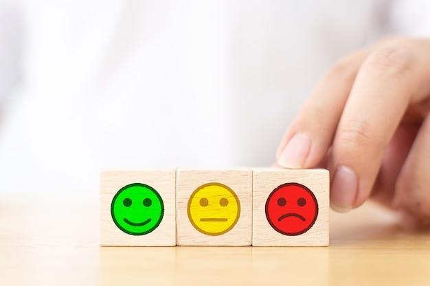 Bliska obraz ręka klienta wybrać smutną twarz znak na drewnianym bloku kostki
