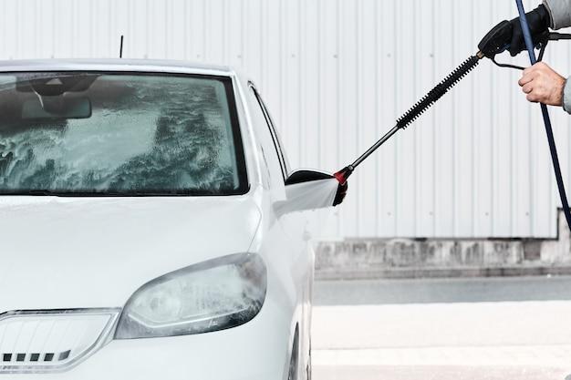 Bliska obsługuje ręczne mycie białego samochodu za pomocą wody pod wysokim ciśnieniem. usługa samo mycia samochodu