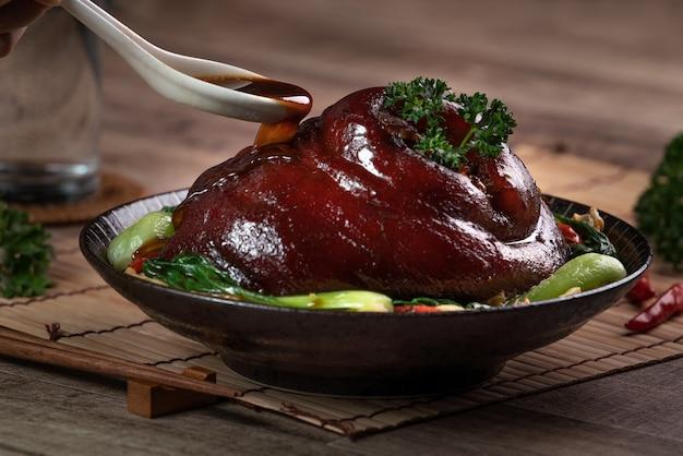 Bliska odlewania pikantny sos sojowy z łyżką na tajwańskiej żywności duszonej golonka wieprzowa w talerzu na tle rustykalnym tabeli.