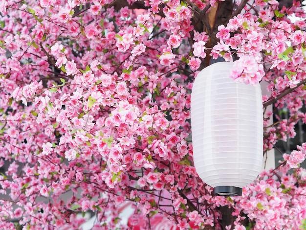 Bliska papierowa latarnia wisząca pod dachem w ogrodzie z różowymi kwiatami sakury. chińska dekoracja nowego roku w parku.