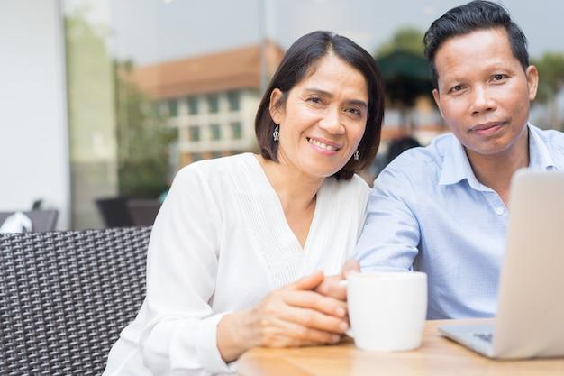Bliska para starszy gospodarstwa strony razem na zewnątrz kawiarni w czasie relaksu, styl życia osób w wieku koncepcji