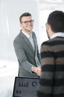 Bliska partnerzy biznesowi uścisk dłoni w nowoczesnym biurze