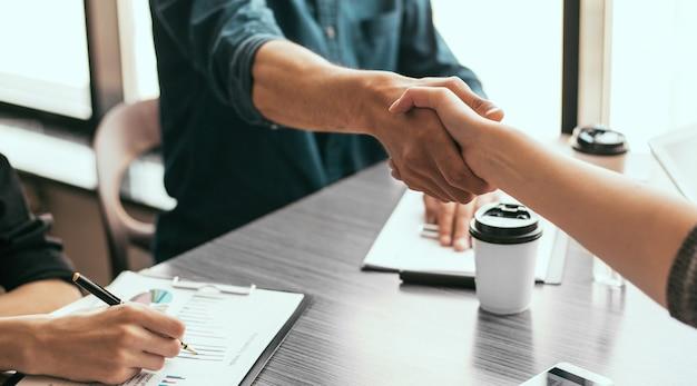 Bliska partnerzy finansowi ściskający ręce nad biurkiem