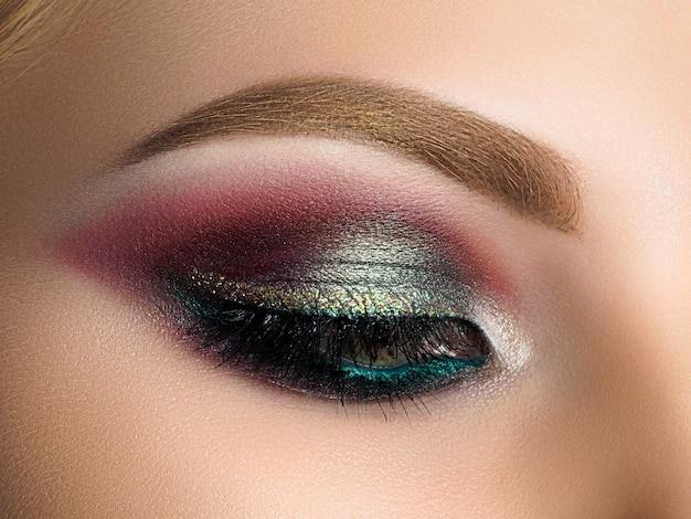 Bliska piękna kobieta oko z wielobarwnym makijażem smokey eyes. makijaż nowoczesnej mody.