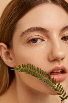 Bliska piękna kobieta pozuje z rośliną