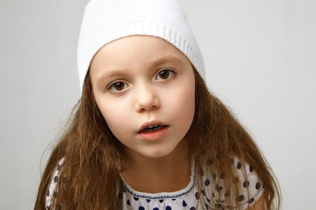 Bliska piękna mała dziewczynka przedszkolak z dużymi brązowymi oczami i luźnymi włosami, pozowanie na biało