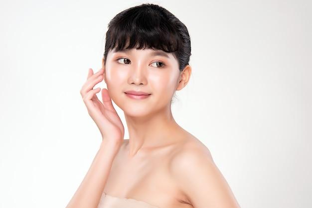 Bliska piękna młoda azjatykcia kobieta dotyka jej czystą twarz ze świeżymi kosmetykami kosmetycznymi świeżej zdrowej skóry i pojęciem traktowania twarzy