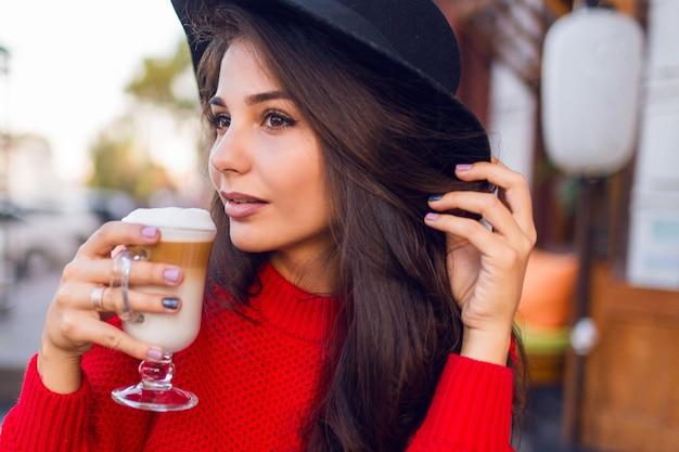 Bliska piękna młoda brunetka kobieta w stylowym czarnym kapeluszu i jasnoczerwonym swetrze siedzi w kawiarni na otwartej przestrzeni i pić kawę z mlekiem lub cappuccino w słoneczny poranek.