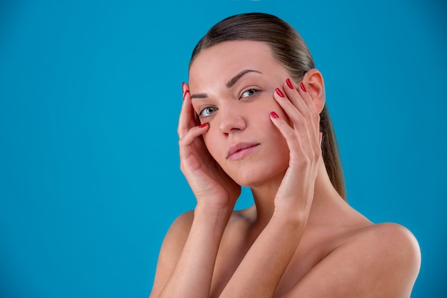 Bliska piękno portret młodej kobiety brunetki uśmiechając się i dotykając jej twarz na niebiesko. idealna świeża skóra. pielęgnacja młodzieży i skóry.