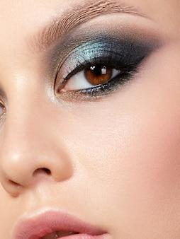 Bliska piękno portret młodej kobiety z piękny makijaż moda. nowoczesny makijaż mody. kolorowe smokey eyes. ekstremalne zbliżenie, częściowy widok twarzy