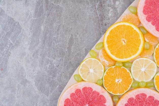 Bliska plasterki owoców cytrusowych i winogron na desce.