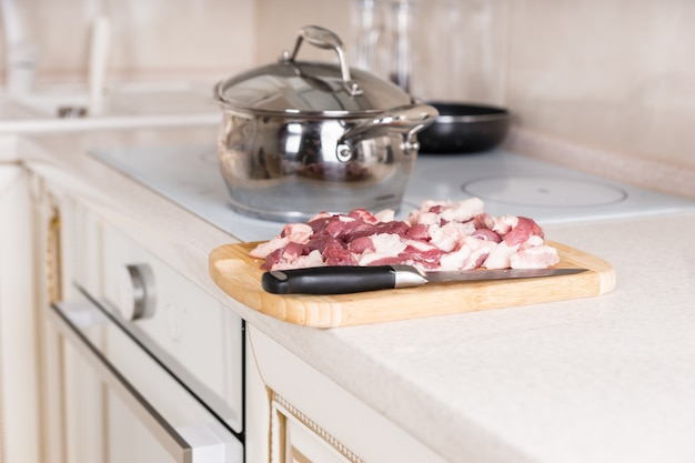 Bliska plastry surowego mięsa i nóż na drewnianą deskę do krojenia w pobliżu pieca w kuchni.