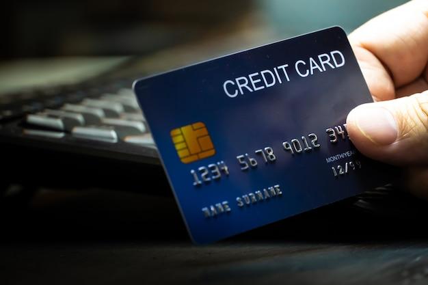 Bliska płytka ostrość ręka trzymać kartę kredytową na klawiaturze komputera