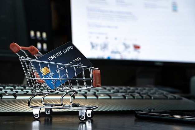 Bliska płytki fokus karta kredytowa w mini karcie zakupowej z klawiaturą komputerową