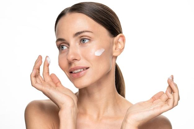 Bliska półnaga kobieta nakładająca serum przeciwzmarszczkowe przeciw starzeniu, nawilżający liftingujący odżywczy krem na dzień na nieskazitelną skórę.