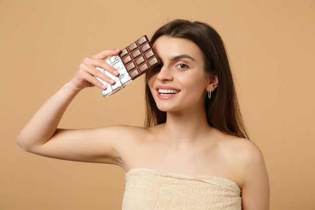Bliska półnaga kobieta o idealnej skórze, nagi makijaż trzyma tabliczkę czekolady odizolowaną na beżowej pastelowej ścianie