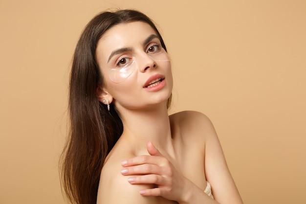 Bliska półnaga kobieta o idealnej skórze, nagie łaty do makijażu pod oczami na beżowej pastelowej ścianie