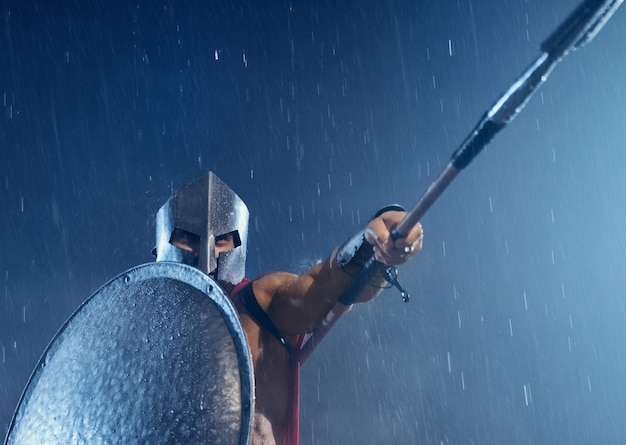 Bliska półnagi spartan w zbroi i czerwonym płaszczu, walczący na zewnątrz z włócznią. widok z przodu mężczyzny w kasku ukrywającego ciało za żelazną osłoną i wskazującego broń w złej pochmurnej pogodzie deszczowej.