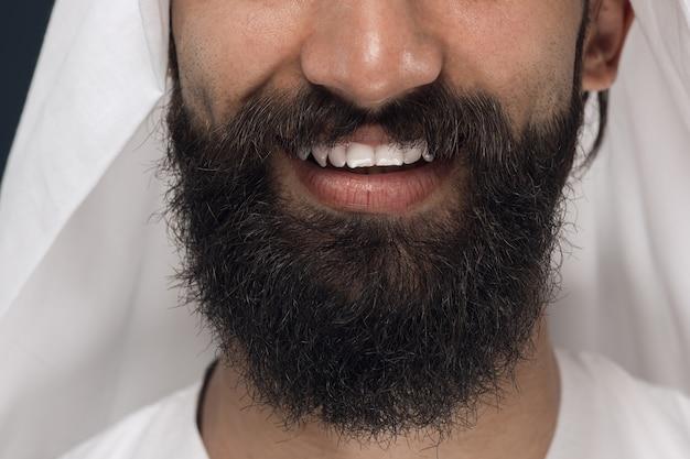 Bliska portret arabskiego saudyjskiego biznesmena na ciemnoniebieskiej przestrzeni. młody mężczyzna twarz modelu z brodą, uśmiechając się