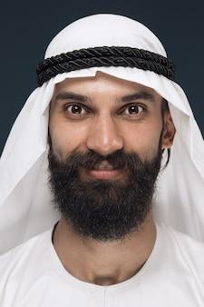 Bliska portret arabskiego saudyjskiego szejka. młody mężczyzna model stojący i uśmiechnięty, wygląda na szczęśliwego.