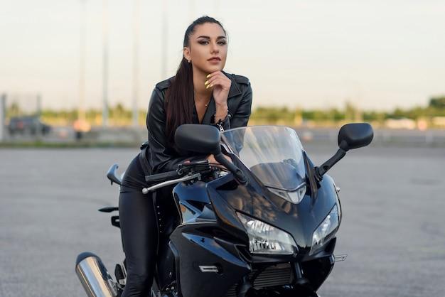 Bliska portret atrakcyjnej dziewczyny w czarnej skórzanej kurtce i spodniach na parking na zewnątrz ze stylowym motocyklem sportowym o zachodzie słońca.