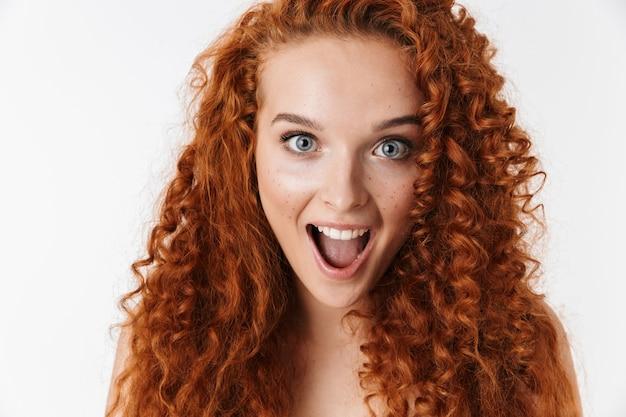 Bliska portret atrakcyjnej podekscytowanej młodej kobiety z długimi kręconymi rudymi włosami stojącej na białym tle, krzywiąc się