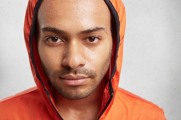 Bliska portret atrakcyjny młody człowiek nosi kaptur, będąc mokrym do skóry po uruchomieniu w deszczową pogodę