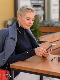 Bliska portret bizneswoman w średnim wieku przy użyciu telefonu na zewnątrz