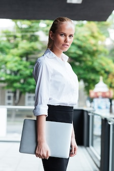 Bliska portret blond bizneswoman trzymającej laptopa stojąc na balkonie na zewnątrz