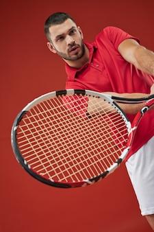 Bliska portret brodaty kaukaski muskularny męski tenisista w czerwonej koszuli trening w klubie sportowym