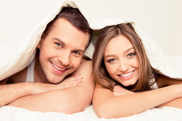 Bliska portret całkiem mężczyzny i kobiety leżącej pod kocem