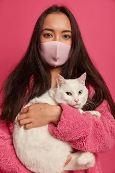 Bliska portret całkiem młoda kobieta ubrana w maskę ochronną na białym tle