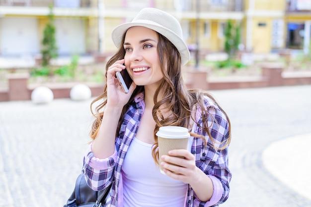 Bliska portret całkiem pięknej, mądrej radosnej uroczej uroczej dziewczyny z promiennym zębatym uśmiechem, wzywająca rodzinę przyjaciół po przerwie w pracy, trzymając w rękach herbatę latte na wynos