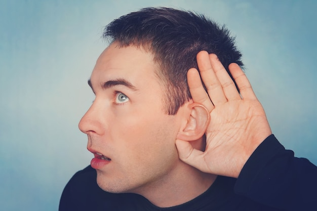 Bliska portret ciekawy zainteresowany zachwycający zabawny zdumiony wesoły zaskoczony mężczyzna trzymając rękę w pobliżu ucha i próbuje usłyszeć informacje na niebieskim tle. zły słuch