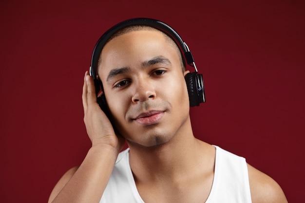 Bliska portret ciemnoskóry student płci męskiej na sobie czarne słuchawki bezprzewodowe, przygotowując się do egzaminów, słuchając wykładu audio, zakrywając jedno ucho ręką. ludzie, technologia, elektroniczne gadżety