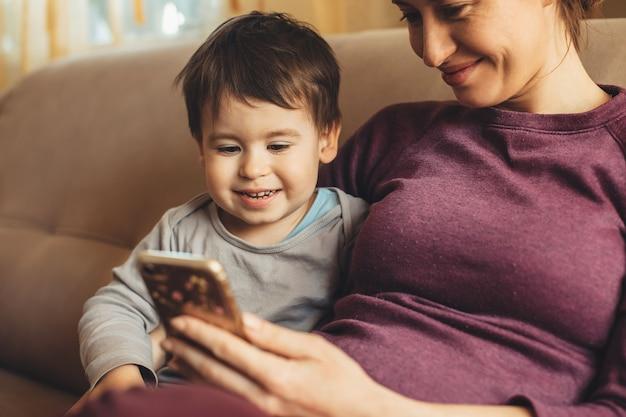Bliska portret ciężarnej matki kaukaskiej spędzającej czas z małym chłopcem przy użyciu telefonu na kanapie
