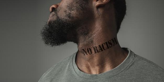 """Bliska portret czarnego mężczyzny zmęczonego dyskryminacją rasową ma na szyi wytatuowane hasło """"żadnego rasizmu"""". pojęcie praw człowieka, równości, sprawiedliwości, problemu przemocy, dyskryminacji. ulotka."""